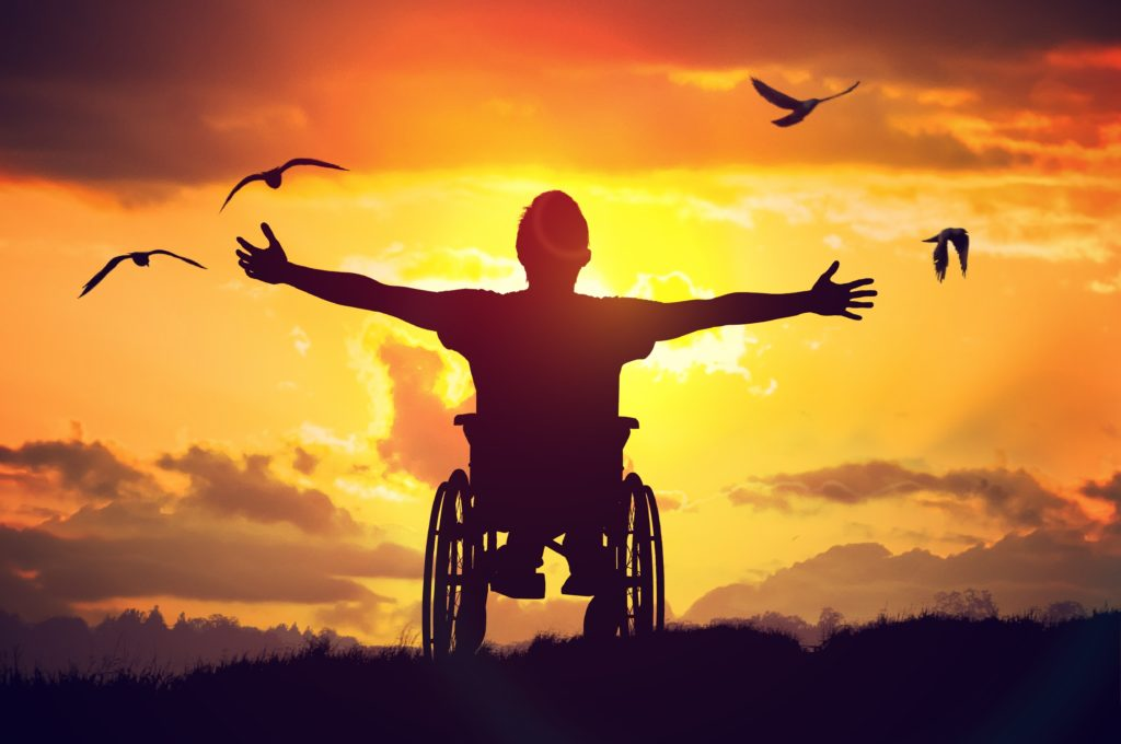 Patient in wheelchair celebrating sunset