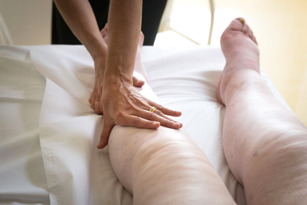therapist using lymphatic drainage on swollen legs