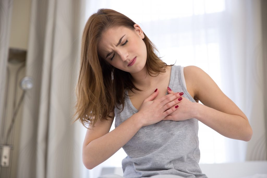 Lady clutching chest with pained look