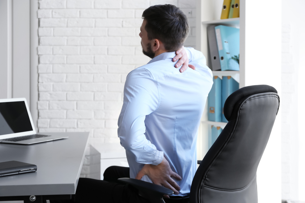 Man sitting at desk with sore back