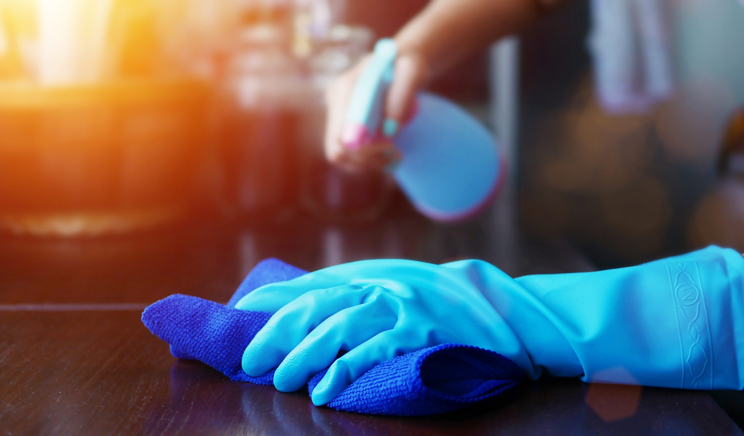 Gloved hands sterilizing surface due to virus
