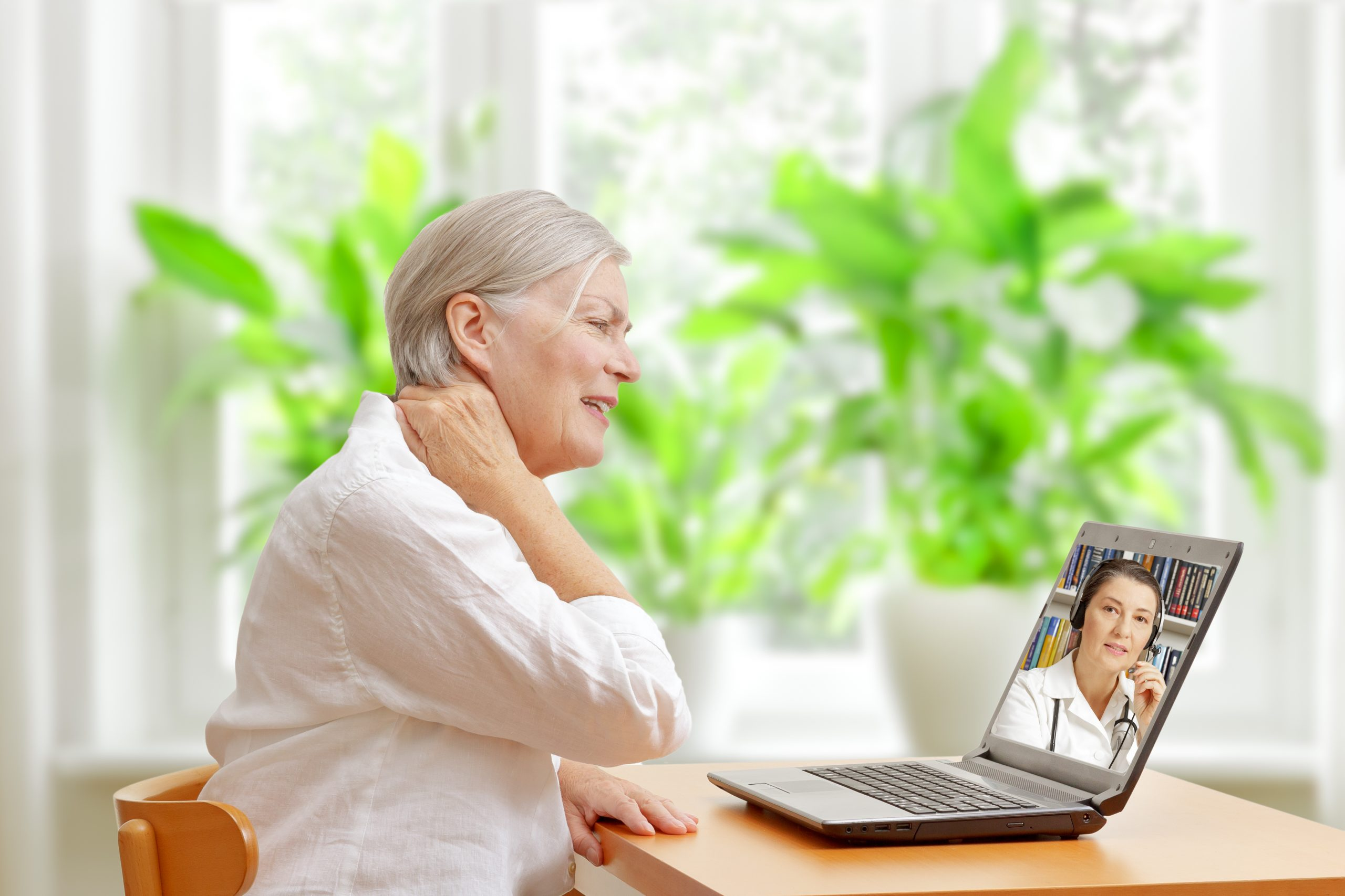 Woman with sore neck doing Telehealth consult due to Virus